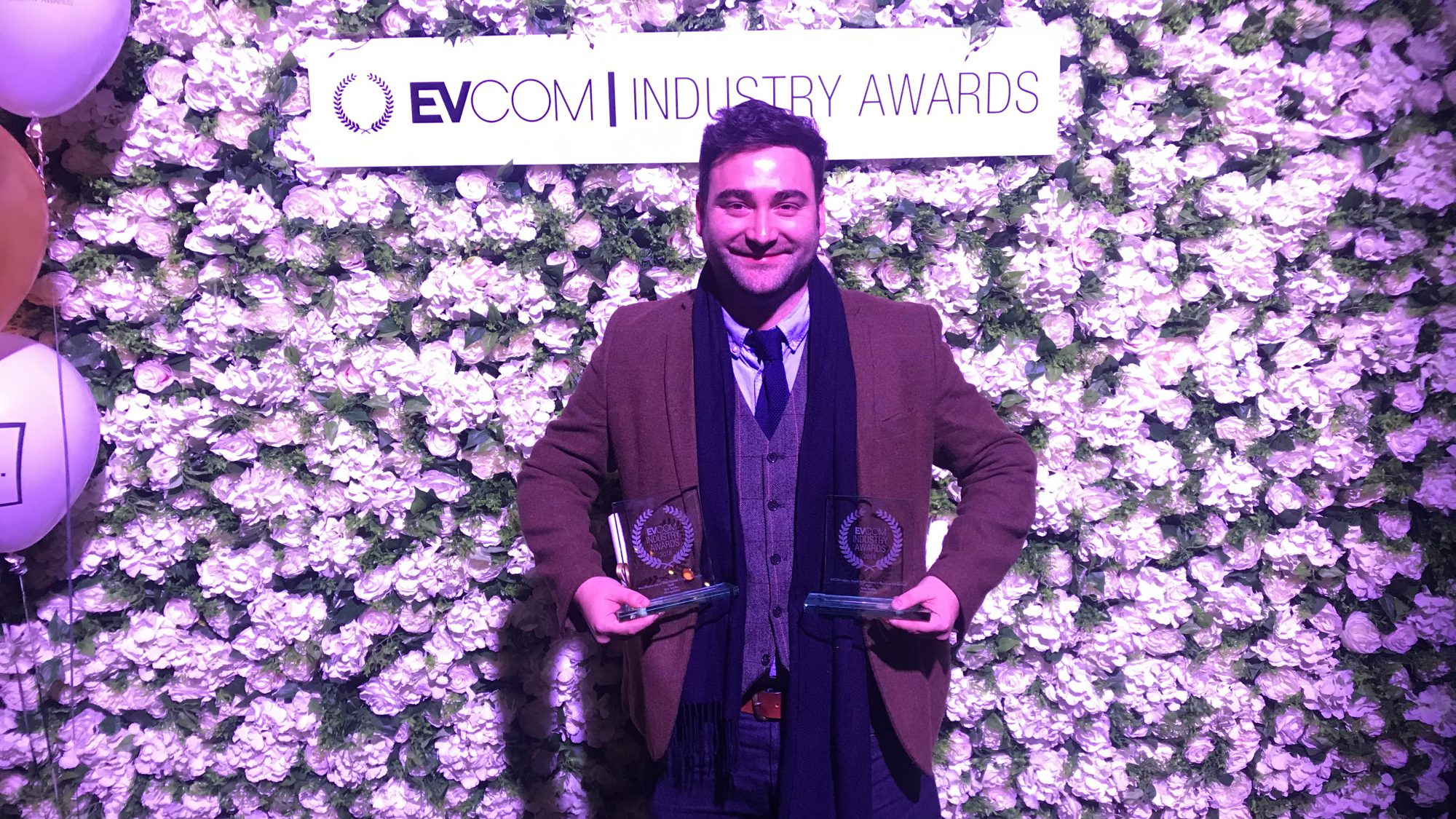 Raw London's Creative Lead holding trophies at EVCOM Awards 2018