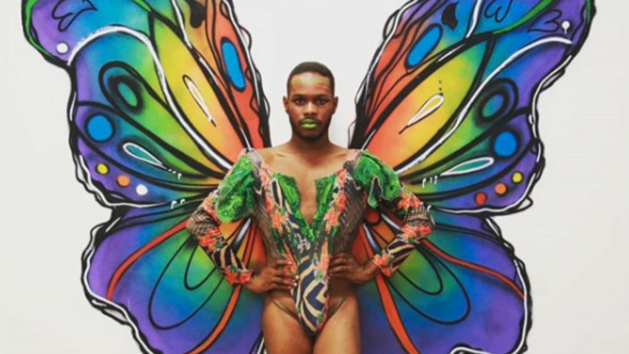 Man in brightly coloured body paint with butterfly wings