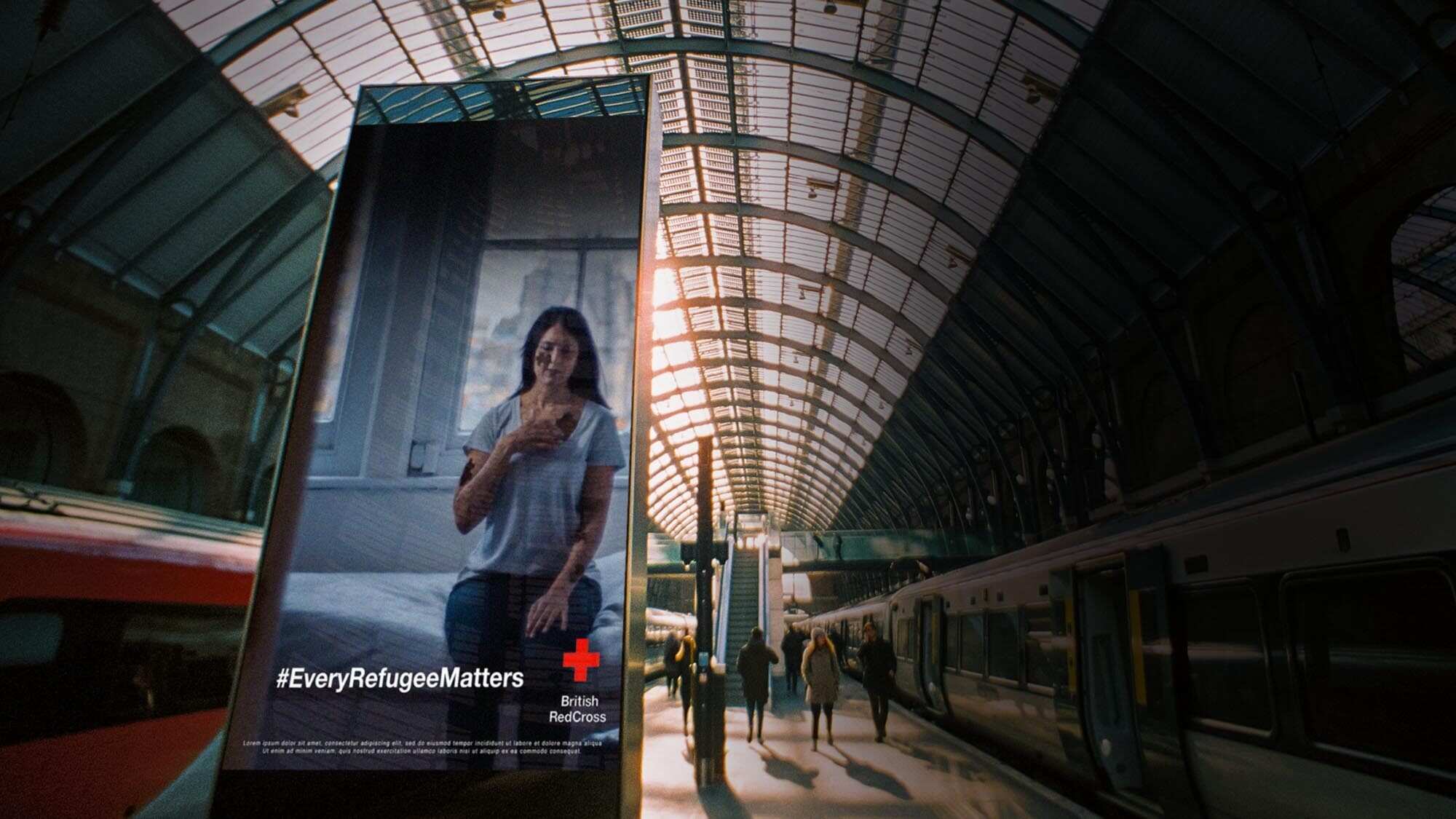 An out-of-home advert in a train station displaying British Red Cross #RefugeeWeek video campaign