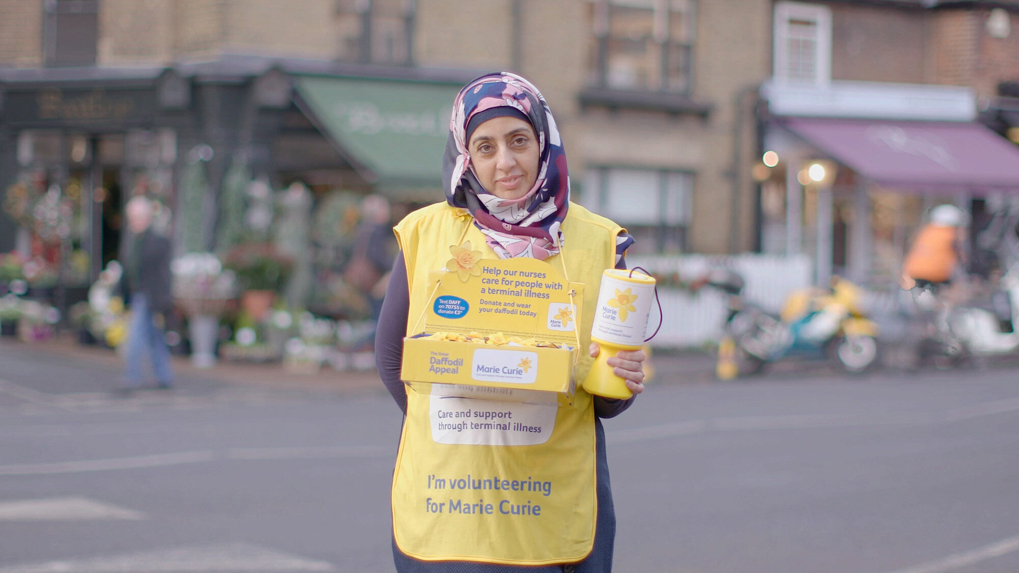 A fundraiser wearing a yellow overall from Marie Curie's social content campaign