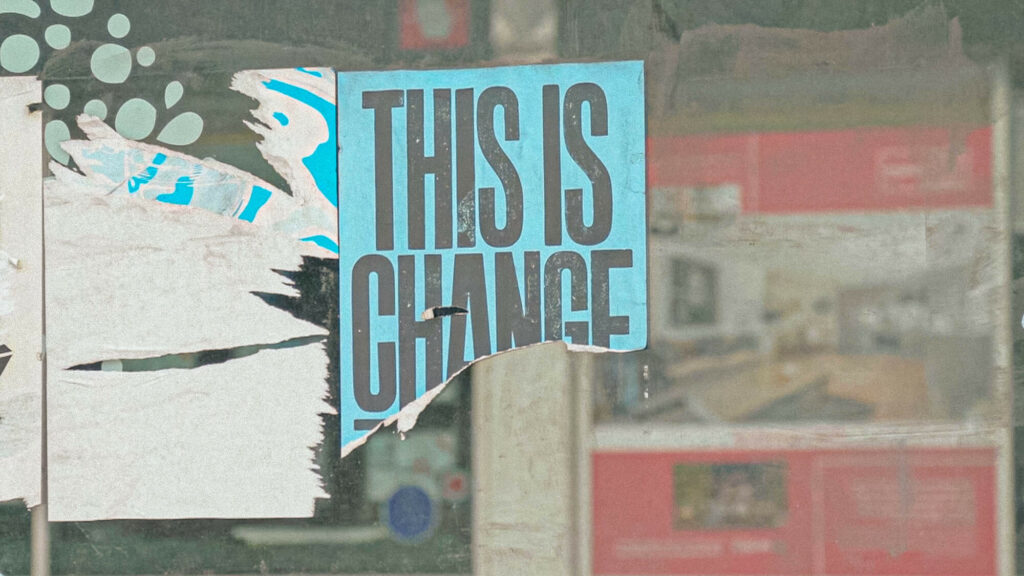 A torn sign in a shop window reads: 'THIS IS CHANGE' during lockdown