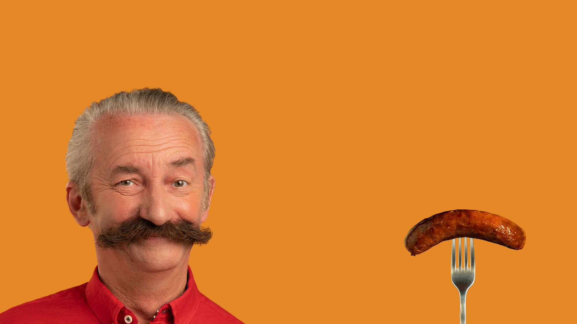 Man with a moustache twinning with a sausage on an orange background as part of FareShare's food campaign