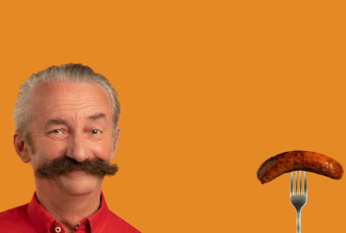 Man with a moustache twinning with a sausage on an orange background as part of FareShare