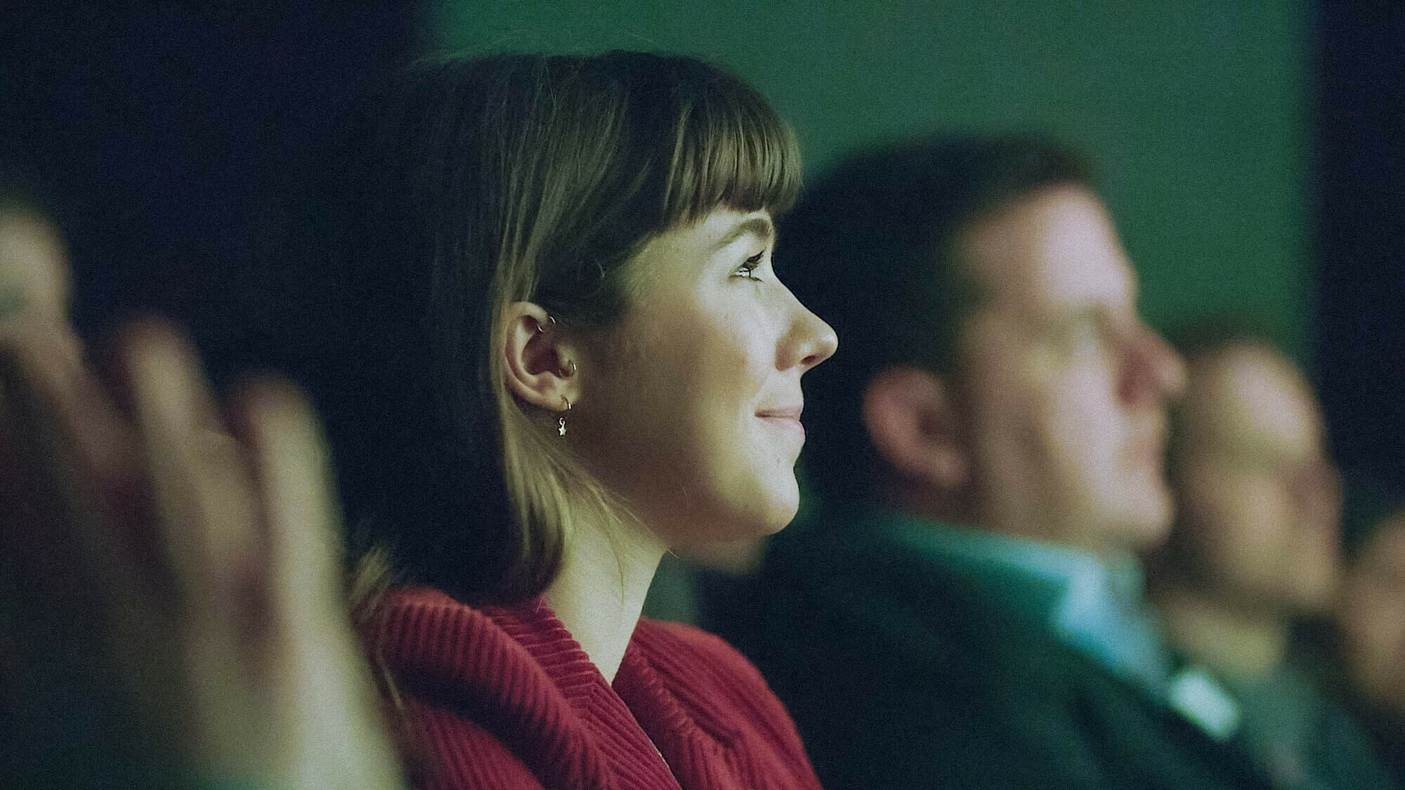 Woman in an audience smiling at a Relay event by Raw London